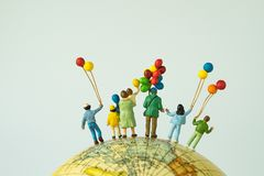 miniature people figure back view of happy family holding balloons standing on globe as looking into the universe or happy stock images
