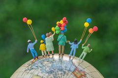 Miniature People Figure Back View Of Happy Family Holding Balloons Standing On Globe As World Climate Change Environment Or Happy Stock Images