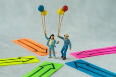 Miniature people figure couple holding balloons standing at the. Center of arrows pointing to them in all directions as people center concept Stock Photo