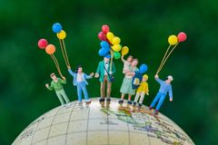 Miniature people figure happy family holding balloons standing o. N united states of america map on globe as world climate change or happy family concept Stock Photos