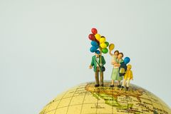 Miniature people figure happy family holding balloons standing o. N united states of america map on globe as world climate change or happy american family Royalty Free Stock Photography