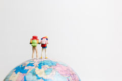 Miniature people figure  standing on the globe world map. With white background and copy space as travel concept Stock Photos