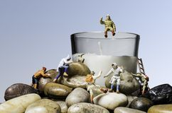 Miniature People Figures Climbing Rocks and Candle stock photography