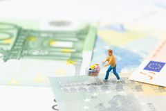 Miniature people figurine with grocery in the shopping cart trolley walking on the bridge through Euro sign on Euro banknotes us royalty free stock images