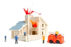 Firefighters with water pistols are taking care of a fire emergency. Miniature people : Firefighters with water pistols are taking care of a fire emergency royalty free stock photography