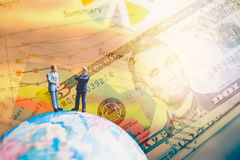 Miniature people on the globe world map with  graph and dollars Royalty Free Stock Photography