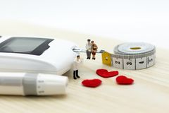 Miniature people: Glucose meter with lancet. Image use for medicine, diabetes, health care concept.  stock photos