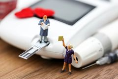 Miniature people : with glucose meter and lancet using as background medicine, diabetes, glycemic, health care, people concept. stock photos