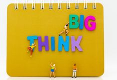 Miniature people : Group Athletes climb on book with THINK BIG text wooden. Image use for Activities, travel, business concept. Miniature people : Group Stock Images