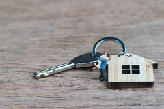 Miniature people happiness couple standing with house key chain. On wooden table using as mortgage or real estate concept Stock Photography