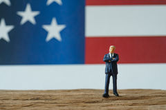 miniature people, happy american businessman standing on wood fl Royalty Free Stock Photo
