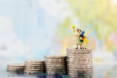Miniature people: Happy family standing on coins stack, money sa Stock Photos