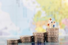 Miniature people: Happy family standing on coins stack, money sa Royalty Free Stock Photos