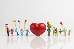 Miniature people happy love family holding balloons with red hea. Rt shape on white background using as happy valentine`s day concept royalty free stock image
