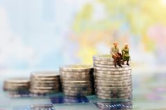 Miniature people: Happy senior couple sitting on coins stack. Money saving growth. Retirement,  emergency plan  and Financial Concept Royalty Free Stock Photography