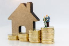 Miniature people: Happy senior couple standing on coins stack wi stock photo