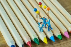 Miniature people holding balloons standing on color pencils pile stock image