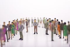 Miniature people in line across to each other with bosses in the. Middle over white background Royalty Free Stock Images