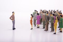 Miniature people in line with boss over white. Miniature people in line with boss over white background Stock Image