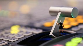 Miniature people : maid cleaning on switcher control of Televisi. On Broadcast,color buttons Royalty Free Stock Photo