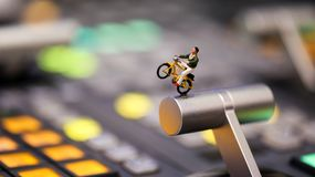 Miniature people : man riding bicycle on switcher control of Tel. Evision Broadcast,color buttons Stock Photo