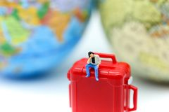 Miniature people : man sitting on red suitcase with mini global. World,Adventure stories,Tourist planning vacation concept Stock Image