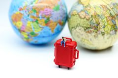 Miniature people : man sitting on red suitcase with mini global. World,Adventure stories,Tourist planning vacation concept Stock Photography