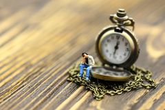 Miniature people : a man sitting with vintage pocket watch on wo. Od background,vintage retro concept Stock Image