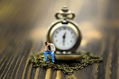 Miniature people : a man sitting with vintage pocket watch on wo. Od background,vintage retro concept Royalty Free Stock Photography