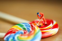 Miniature people : man worker with Colorful of candies and loll. Ipops,education and food concept stock photography