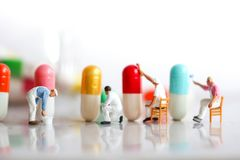 Miniature people : man working on capsule drug using for healthy. Concept Stock Images