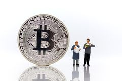 Miniature people : Men reading for find money with bitcoin on white background. Miniature people : Men reading for find money with bitcoin on white background stock photos