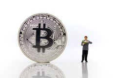 Miniature people : Men reading for find money with bitcoin on white background. Miniature people : Men reading for find money with bitcoin on white background stock photography