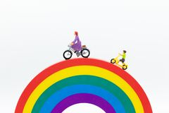 Miniature people : Mom and kids cycling on the rainbow. Image use for to be good model, family concept.  royalty free stock images