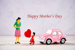 Miniature people: A mother who is given a heart in love by little child girl with little bettle pink car, the concept of Mother`. S Day, blank background for royalty free stock images