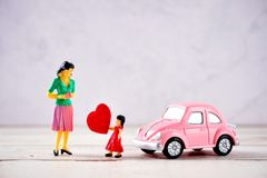 Miniature people: A mother who is given a heart in love by little child girl with little bettle pink car, the concept of Mother`. S Day, blank background for stock photo