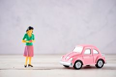 Miniature people: A mother who is given a heart in love by little child girl with little bettle pink car, the concept of Mother`. S Day, blank background for royalty free stock image