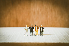 Miniature people, old businessman team. Standing on wooden background using for business and teamwork concept - Vintage filter Stock Photos
