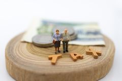 Miniature people, Old couple figure sitting on top of stack coins using as background retirement planning, Life insurance concept. Miniature people, Old couple royalty free stock photography