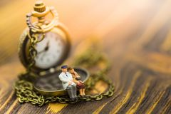 Miniature people: Old couples are sitting on the clock. Image use for spending precious minutes every minute together.  Stock Photo