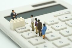 Miniature people Pay queue Annual income TAX for the year on calculator. using as background business concept and finance concep. T with copy space  for your Royalty Free Stock Photos