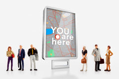 Miniature people  - people standing in front of a billboard with a city map Stock Images