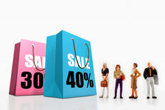 Miniature people  - people standing in front of paper bags with printed big sale. Royalty Free Stock Photography
