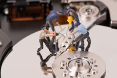 Miniature people repair hard disk drive Stock Photos