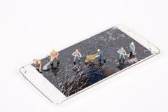 Miniature people repair smartphone crack Royalty Free Stock Photo