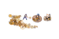 Miniature people repairing clockwork. Teamwork. Help in the work. Working employees. Stock Photo