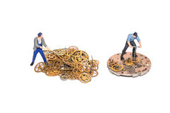 Miniature people repairing clockwork. Teamwork. Working employees. Miniature people repairing clockwork. Teamwork. Help in the work. Working employees. A pile Stock Photo