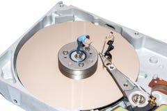 Miniature people repairing the hard drive. A broken computer equipment. Royalty Free Stock Photo