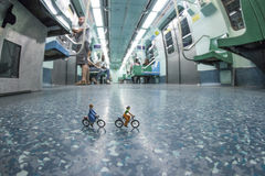 Miniature people riding bicycles in the metro. Stock Image