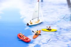 Miniature people, Rowing boat in the ocean. Image use for sports concept.  Royalty Free Stock Photography